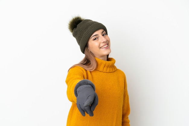 Young girl with winter hat isolated on white pointing front with happy expression
