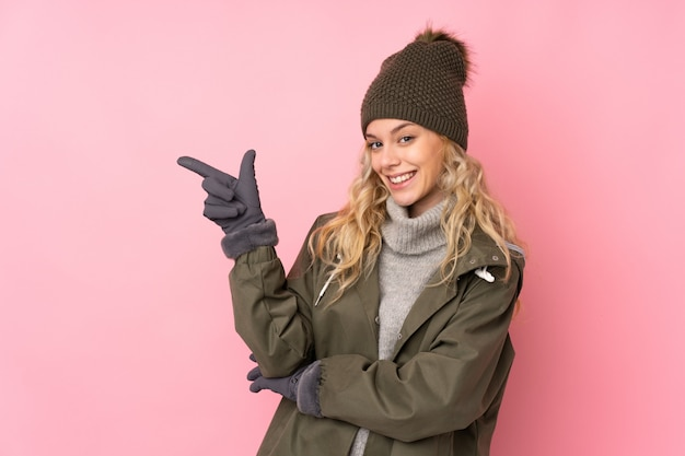 Young girl with winter hat on pink pointing finger to the side