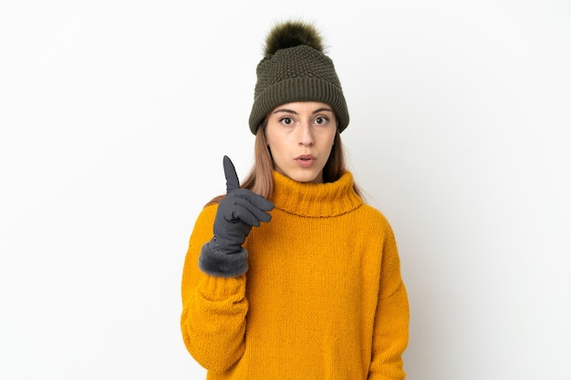 Young girl with winter hat on white intending to realizes the solution while lifting a finger up