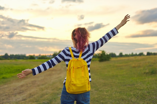 Young girl with yellow backpack, her back with open hands