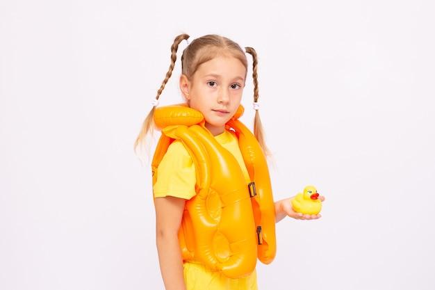 Молодая девушка с желтым спасательным жилетом и резиновой уткой на белом фоне.