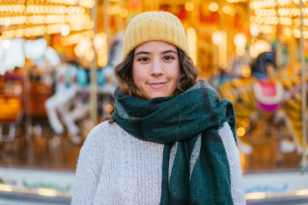 Young girl with yellow wool cap and scarf at a christmas fair