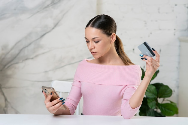 Young girl woman looking at credit bank card paying online in shop, using banking service enter
