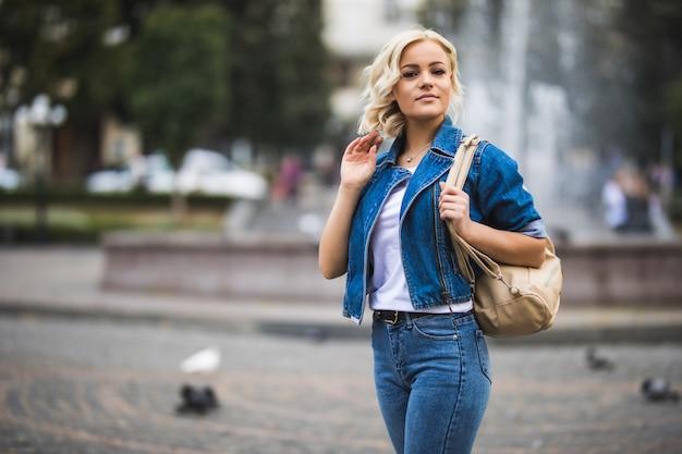 Молодая девушка женщина на уличном квадратном фонтане, одетая в синие джинсы с сумкой на плече в солнечный день