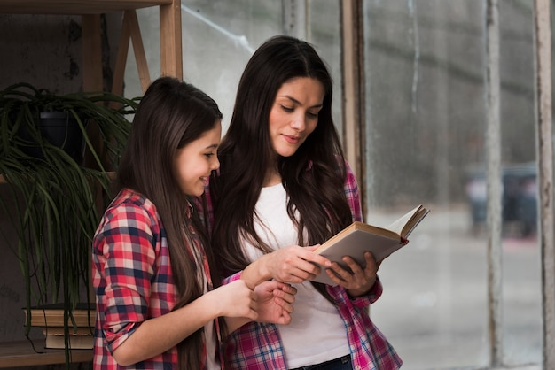 Young girl and woman reading book together