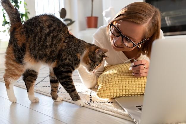 Молодая девушка работает дома, играет с кошкой, студенткой-фрилансером, женщина на дистанционном обучении, ласки