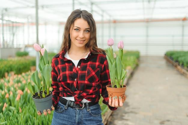 Молодая девушка, рабочий с цветами в теплице