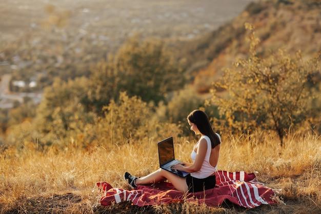 丘の上に日没時にラップトップで働く少女。