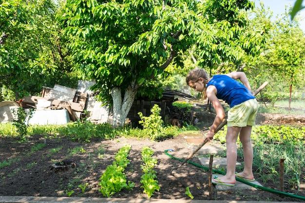 健康的なアウトドアライフスタイルとダイエットの概念で鍬と菜園で働く少女