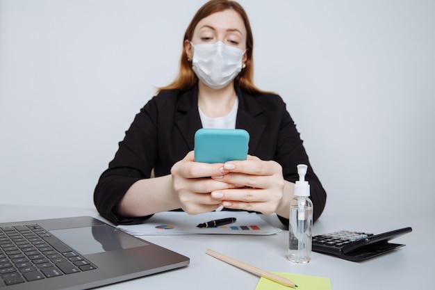 オフィスの机の上のフェイスマスクで働く少女。電卓を使って、スマートフォンで何かアイデアをメモする