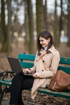 ノートパソコンとベンチの上の公園で働く少女