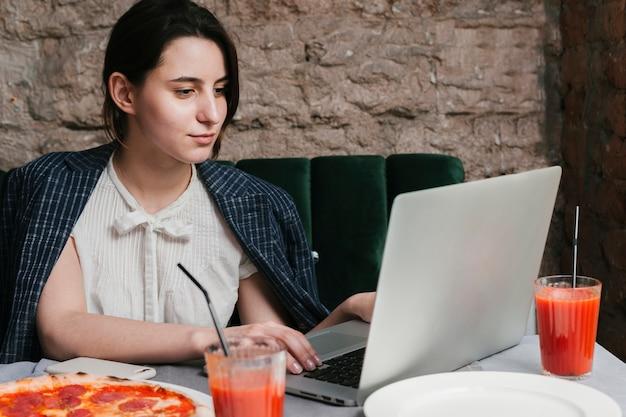 Молодая девушка работает на ноутбуке