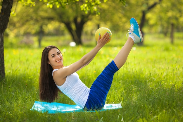 Young girl working out outdoors. beautiful woman doing pilates, yoga and fitness exercices on nature.