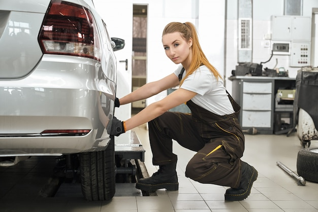 Young girl working in service station with vehicles.