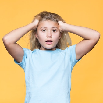 Young girl worried with yellow background