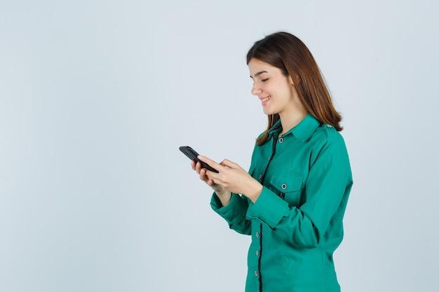 Молодая девушка пишет сообщения по телефону в зеленой блузке, черных штанах и выглядит веселой, вид спереди.