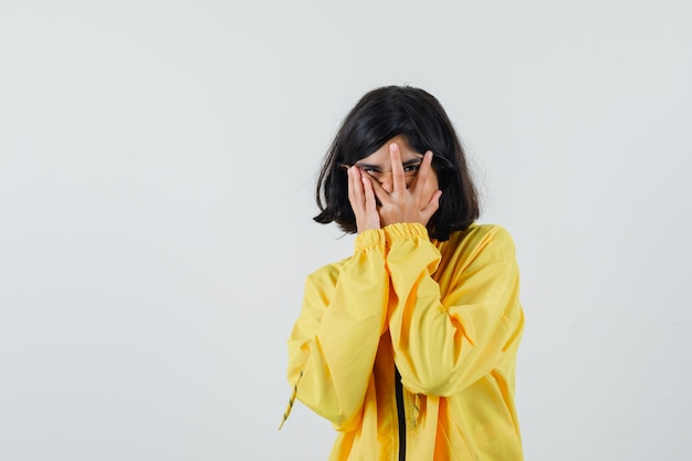 Young girl in yellow bomber jacket looking through fingers and looking happy