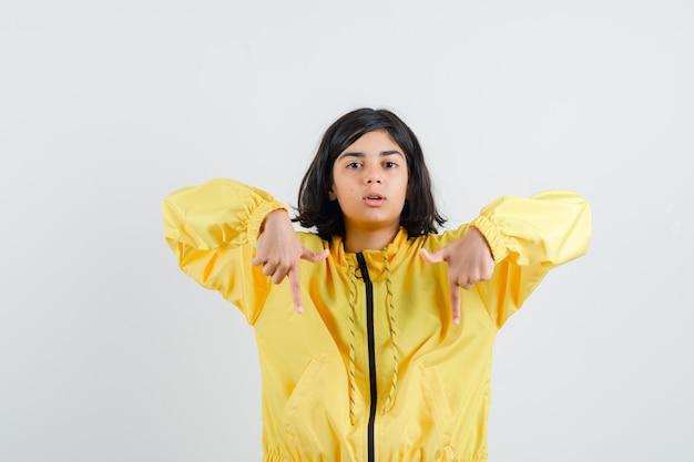 Giovane ragazza in bomber giallo con la punta rivolta verso il basso con il dito indice e che sembra seria