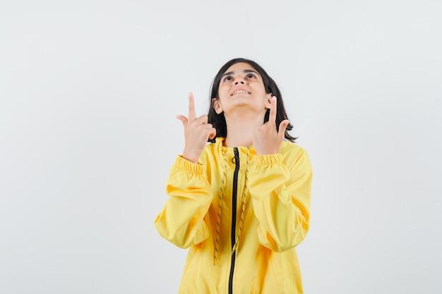 Giovane ragazza in bomber giallo rivolto verso l'alto con le dita indice e guardando felice