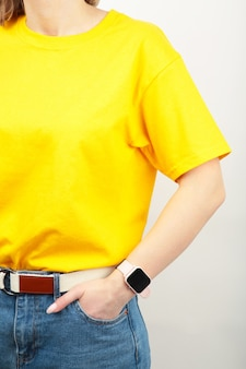 Young girl in yellow t-shirt on a grey surface