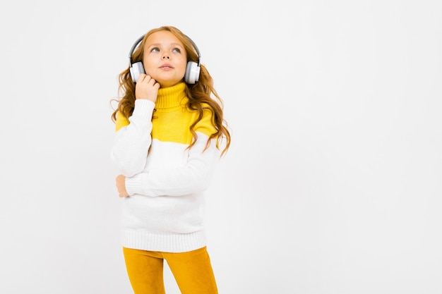 Young girl in a yellow and white sweater listens to music and looks up