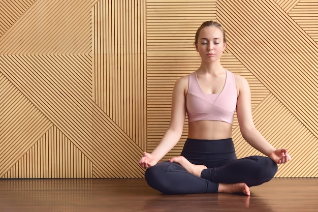 若い女の子のヨガインストラクターがロータスポジションで瞑想します(アルダパドマサナポーズ)