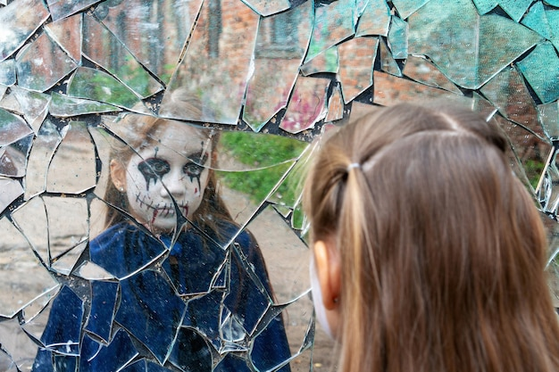 Young girl zombie looks in a broken mirror. the concept of human emotions.