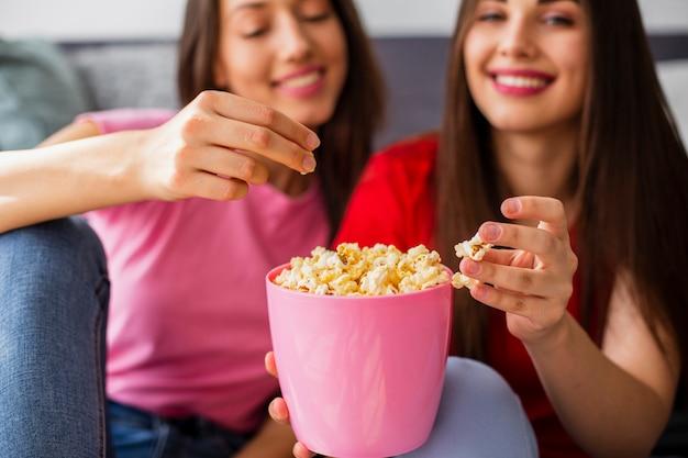 Молодые подружки дома едят попкорн