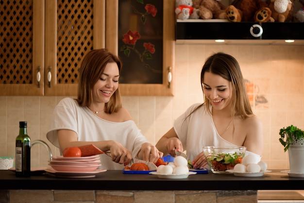 가정 부엌에서 쌍둥이 야채를 자르고 젊은 여자 친구.