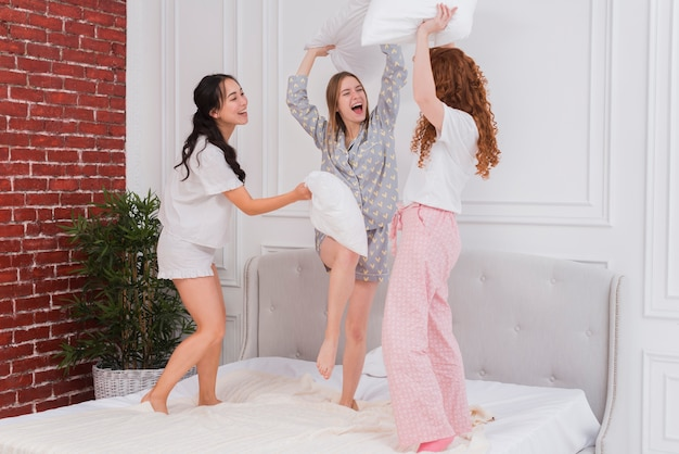 Young girlfriends fighting with pillows