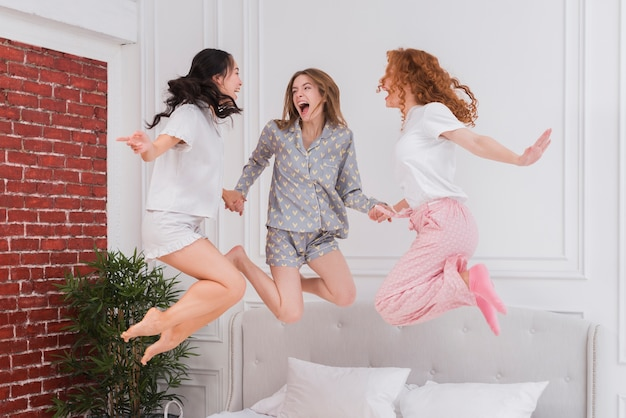 Young girlfriends jumping in bed