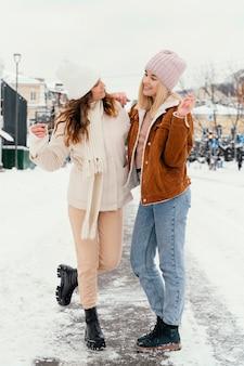 Giovani amiche all'aperto che si guardano l'un l'altro