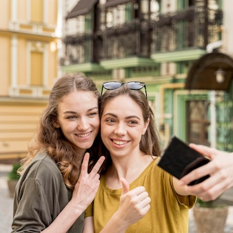 Young girlfriends taking selfie