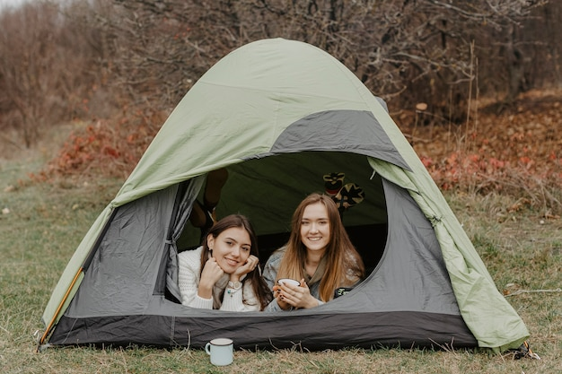 Young girlfriends on winter trip with tent