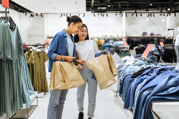Молодые подруги с картонными пакетами, магазин одежды. женщины, делающие покупки в модном бутике, шопоголики, покупатели с покупкой