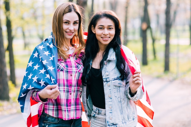 Young girlfriends wrapping in american flag standing outside