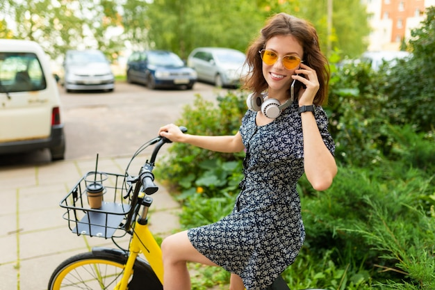 Young girll call the phone and ride a bike in the park with a great mood
