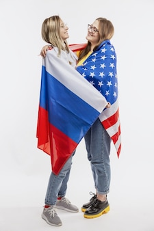 Young girls in american and russian flags laugh and hug.