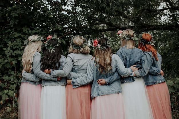 Giovani ragazze in bei vestiti e giacche di jeans nel parco