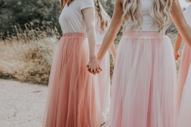 Giovani ragazze in bei vestiti che tengono le mani