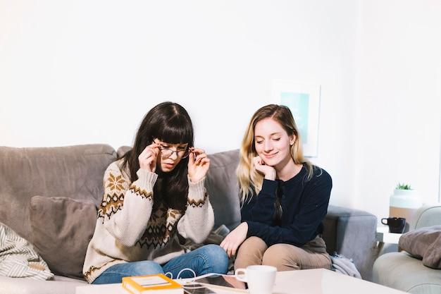 Молодые девушки, отдыхая на диване у себя дома