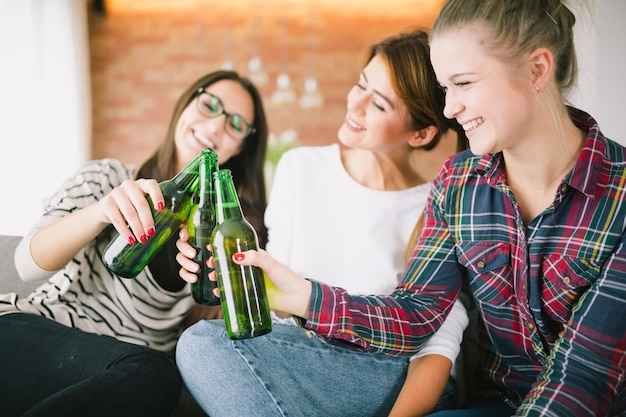 Young girls clinking with beer bottles