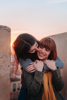 Young girls couple embracing while kissing you on the face
