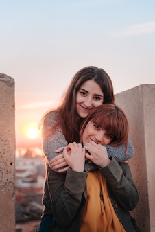 Young girls couple looking at camera while hugging