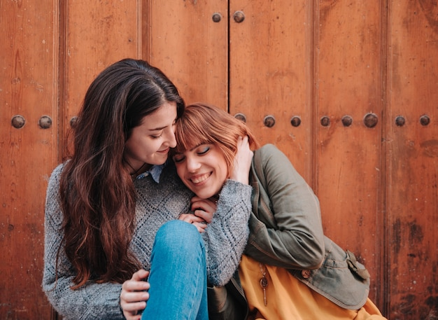 Young girls couple sitting at the door while kissing and being happy