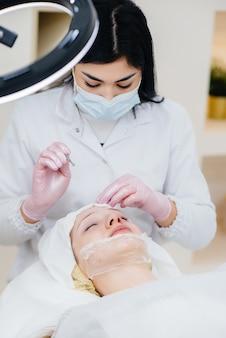 Молодые девушки делают механическую чистку лица в современной косметологической клинике. косметология.