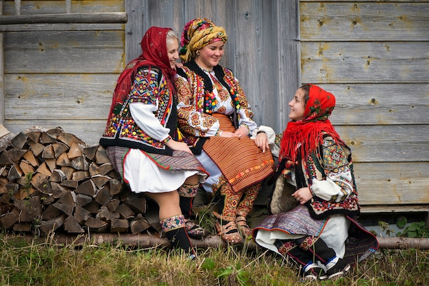 Young girls dressed in ancient picturesque hutsul national clothes. cheerful conversation of three girlfriends.