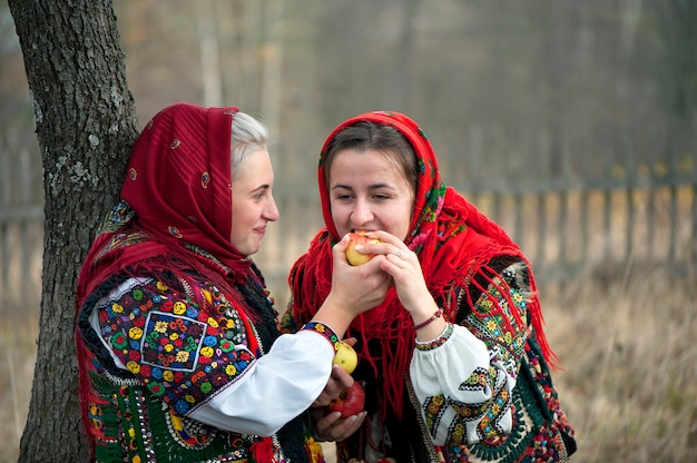 Young girls dressed in ancient picturesque hutsul national clothes eat an apple. ukraine.