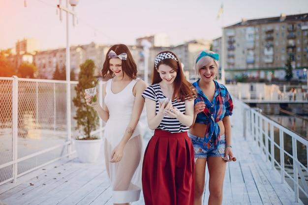 Молодые девушки, одетые в современной моды ходьбе
