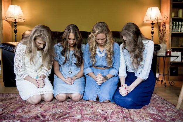 Giovani ragazze una accanto all'altra che guardano giù in una stanza